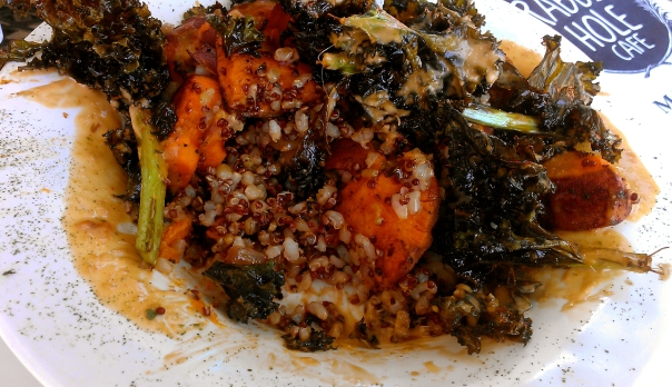 Layered brown rice, quinoa, sweet potato, onions, and kale