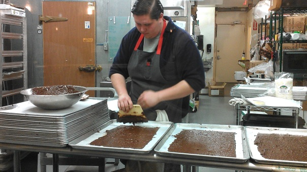Spreading the stone-ground chocolate so it will solidify into bars.